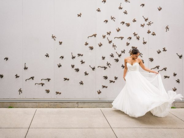 Bride stands in flowing wedding dress in front of a wall covered in bronze frogs leaping around.