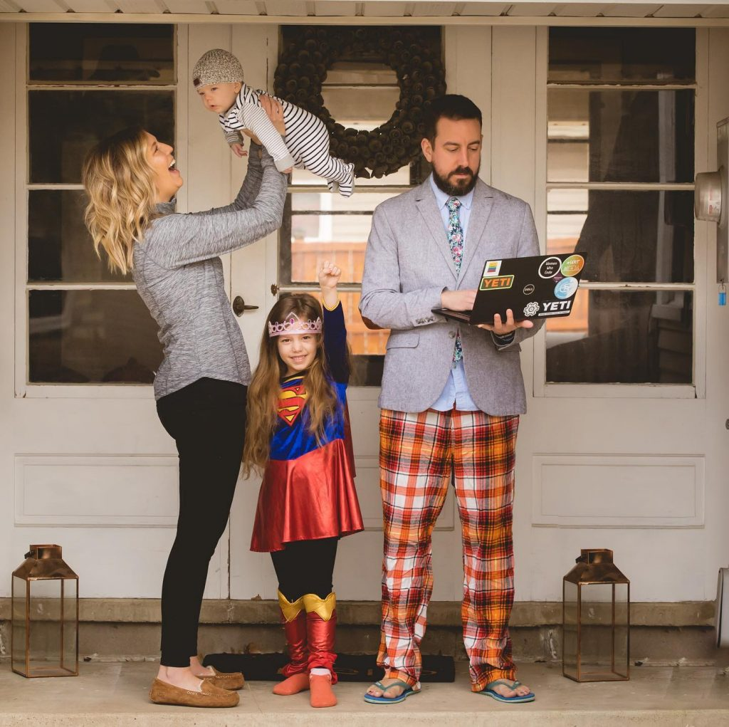 A family of four poses for a photo on their front steps. Mom, wearing biusines casual adn house slippers, holds baby up in the air. Young daughter strikes a superhero pose in her SuperWoman costume. Dad, wearing a suit coat with pajama bottoms and flip flops, fiddles with his laptop.