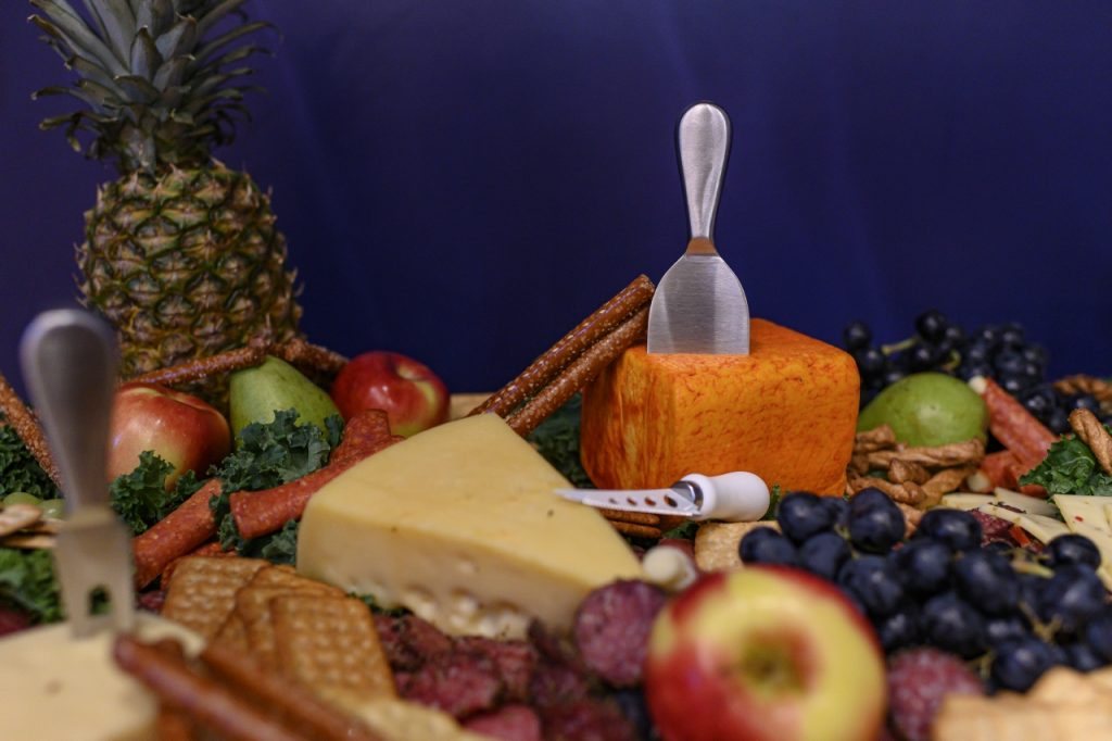 Closeup of fruit and cheese board with pineapple, apples, grapes, crackers, and hunks of cheeses.