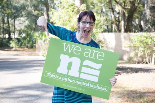 "Photographer Adrienne Fletcher holds a green sign saying ""We Are Neutral: This is a carbon neutral business""."