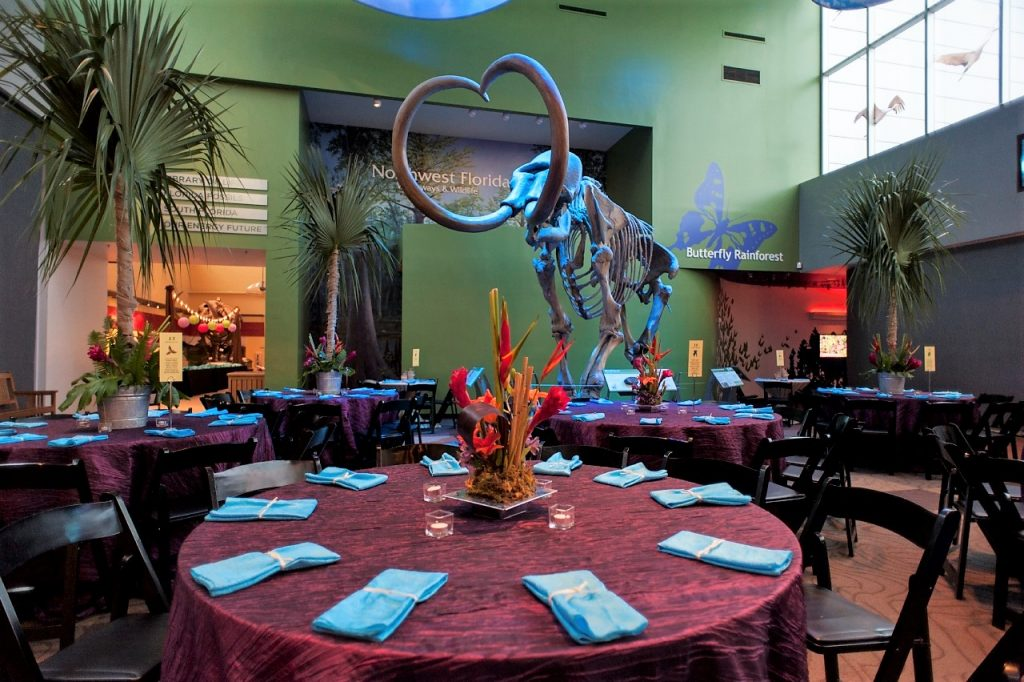 Mammoth surrounded by tables in dark red linens and tropical foliage.