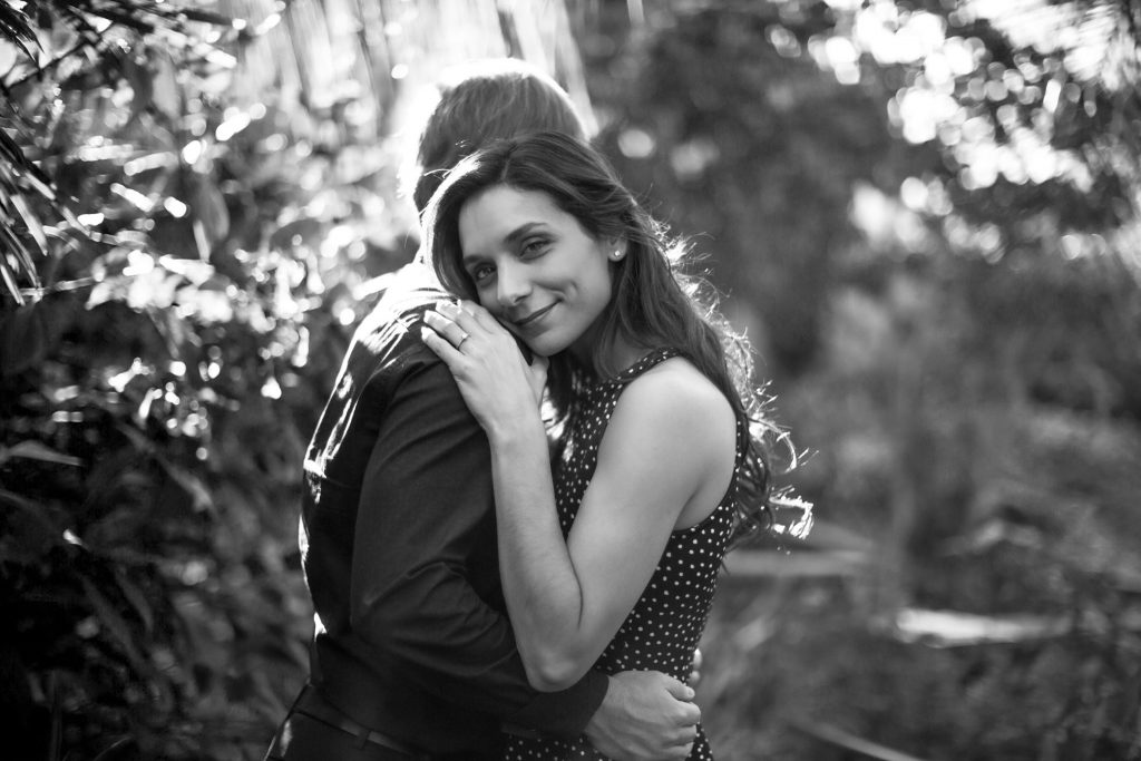 woman with brown hair looks at camera as she hugs man in Butterfly Rainforest