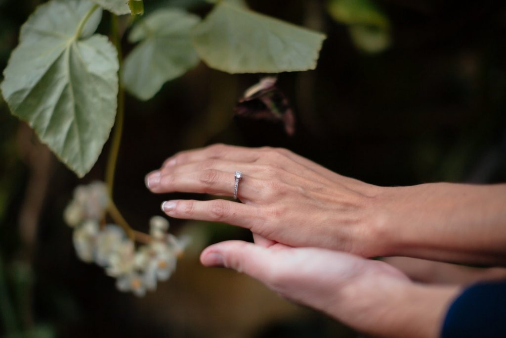 bride shows off ring with plants in background
