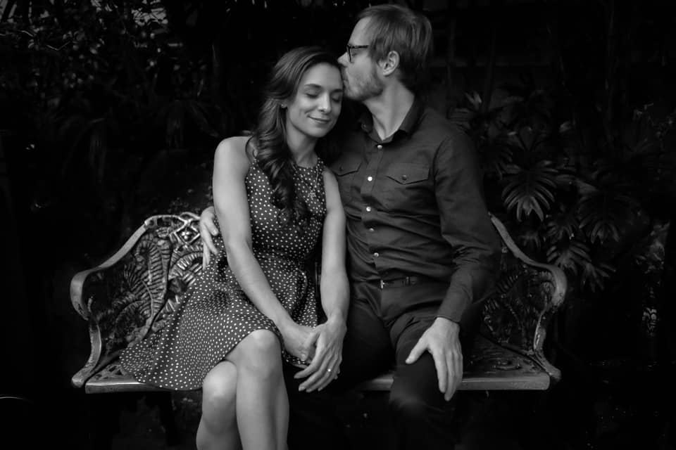black and white - man and woman seated on a bench, he kisses her on the top of the head as she closes her eyes