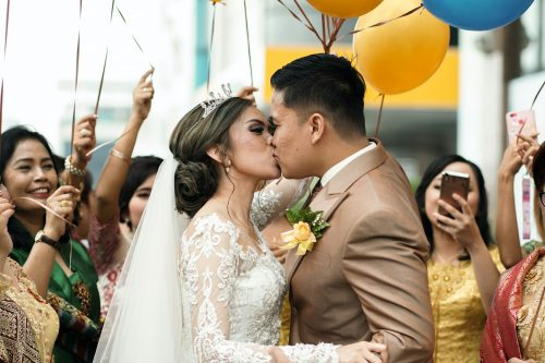 bride and groom kiss while wedding guests holding balloons cheer them on