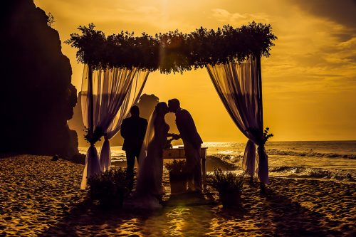 silhouette of a wedding couple kissing under a chuppa at the beach (officiant in background)