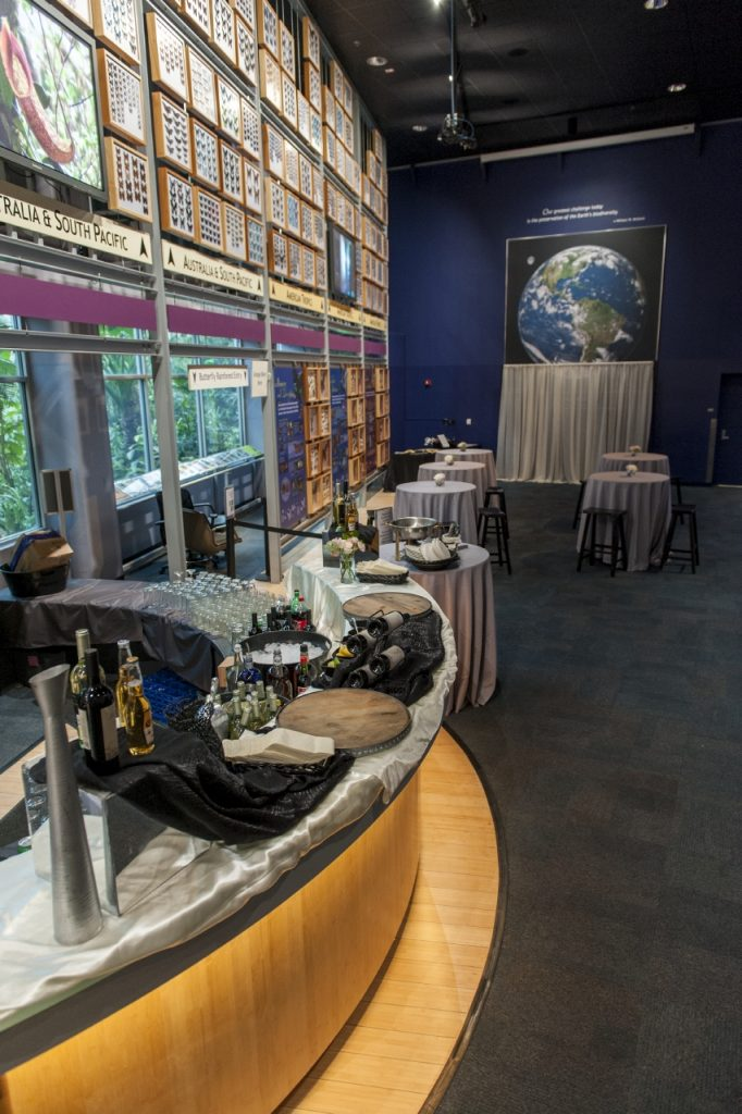 View of Thompson Gallery looking at Earth photo; Rainforest desk as a bar in foreground and pub tables and photobooth backdrop in the distance