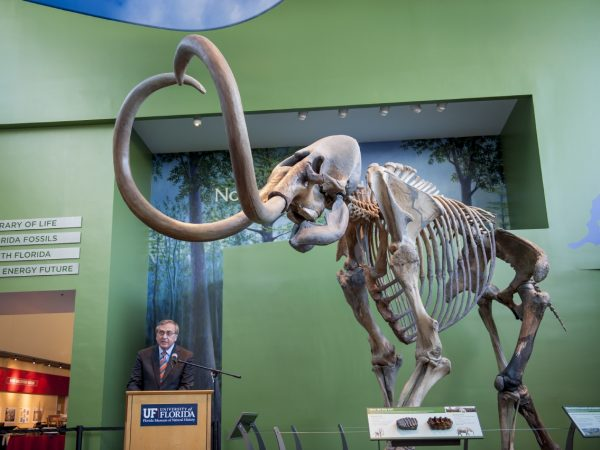 President Fuchs stands at podium in front of mammoth skeleton