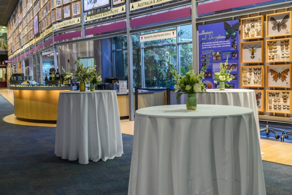 pub tables with white linens and floral centerpieces in Thompson Gallery