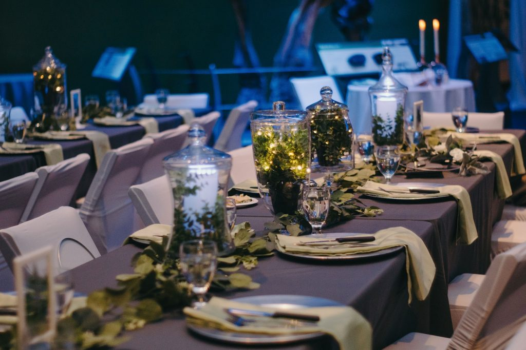 tabletop decor - hurricane laterns and vases filled with candles, greenery, and twinkle lights