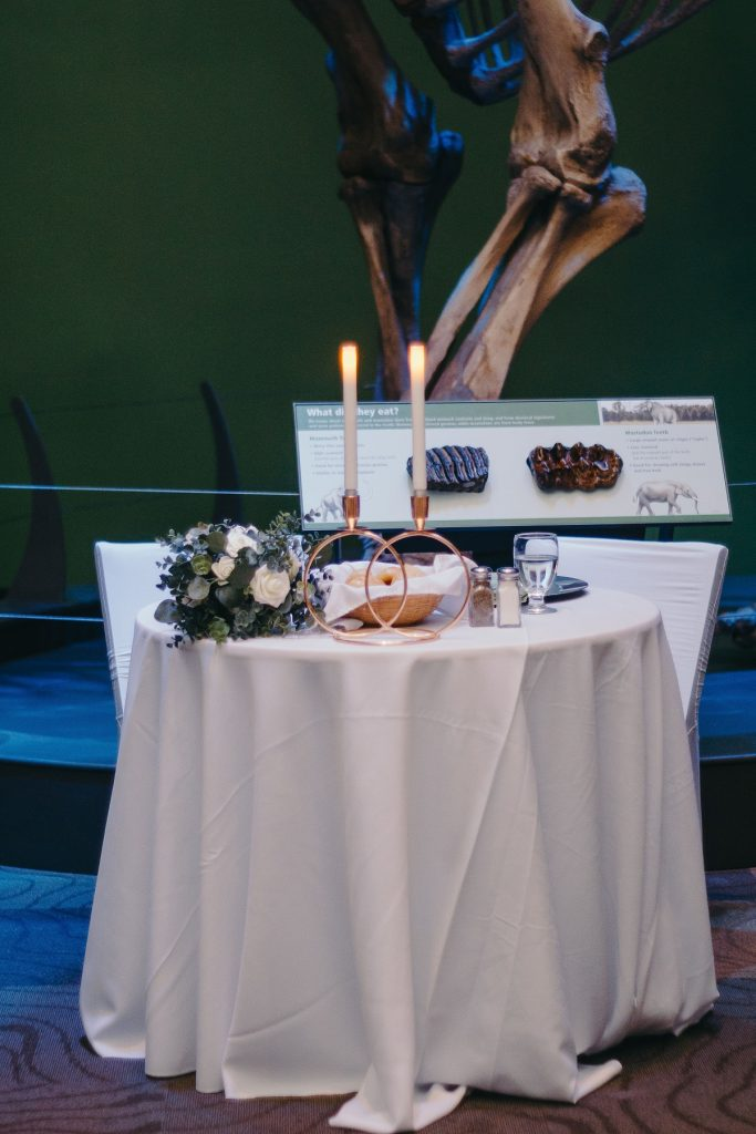 sweetheart table with white tablecloth, two pillar candles, and bride's bouquet