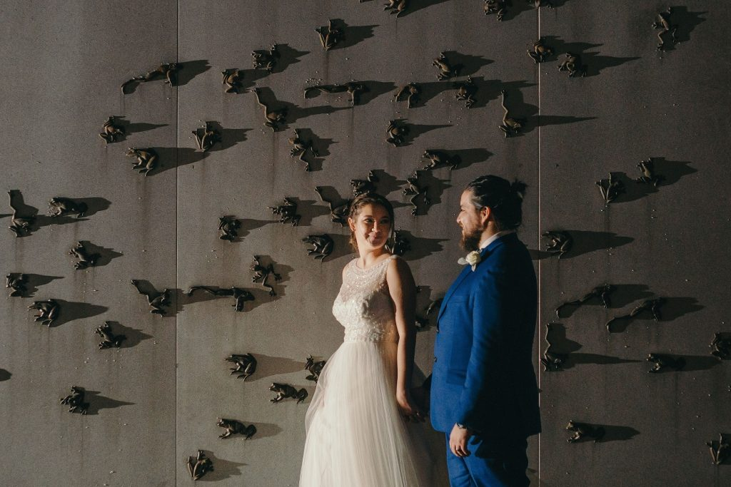 """bride and groom stand in front of """"frog wall"""" on the Museum's patio in the evening - bride looks back at groom"""
