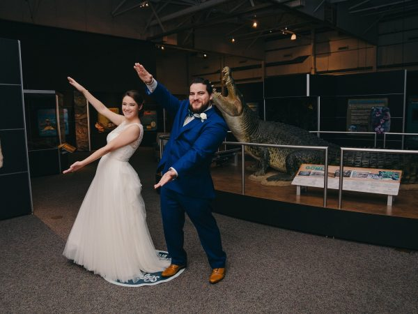 bride and groom do the Gator Chomp in front of a replica of the largest gator to ever live in captivity (in Crocs exhibit)