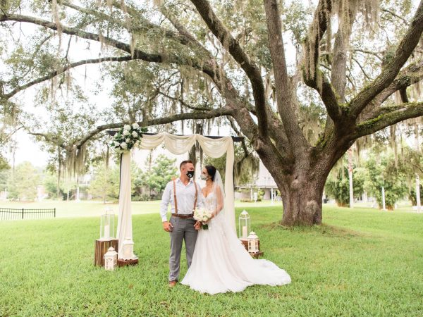 bride and groom wearing masks stand in front of an archway under an oak tree