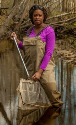person in wading overalls holding a large net and standing a water