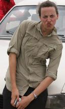 person in a khaki shirt leaning against a car