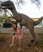 person posing next to a dinosaur statue