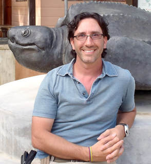 person leaning next to a large turtle statue