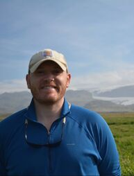 person smiling, mountains can be seen behind them