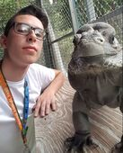 person wearing glasses posing next to a large lizard