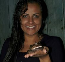 person smiling and holding a frog