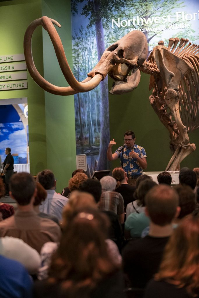 a speaker in front of an audience stands below a mammoth fossil in a museum gallery