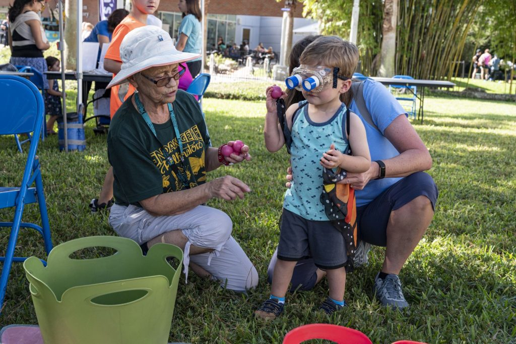 two adults engage with a small child in an outdoor museum activity
