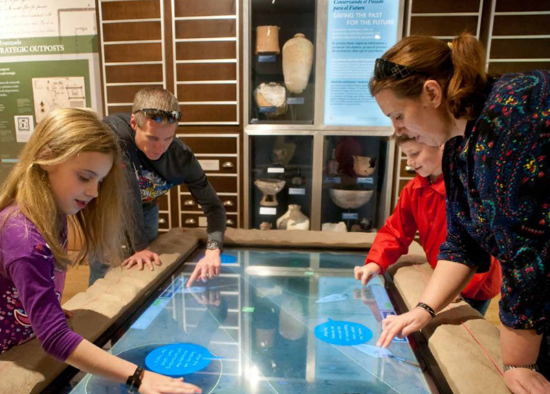 Adults and kids working with interactive First Colony exhibit
