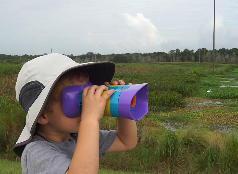 child looking through brightly colored binoculars