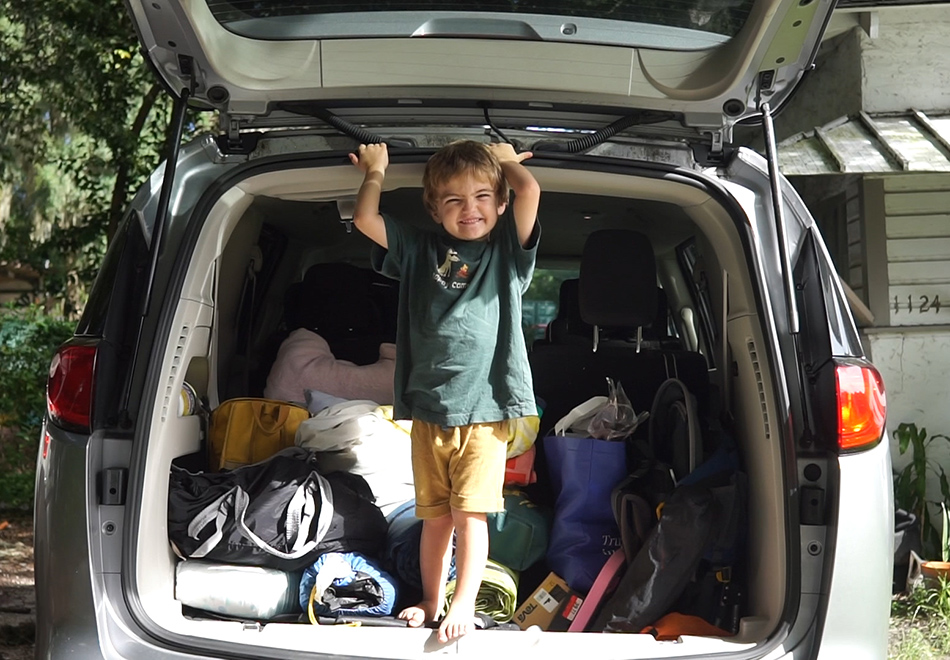 child standing in the back of a car with packed camping equipment behind them