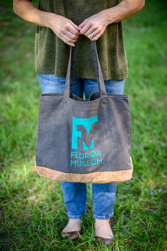 person holding dark canvas bag with Museum logo