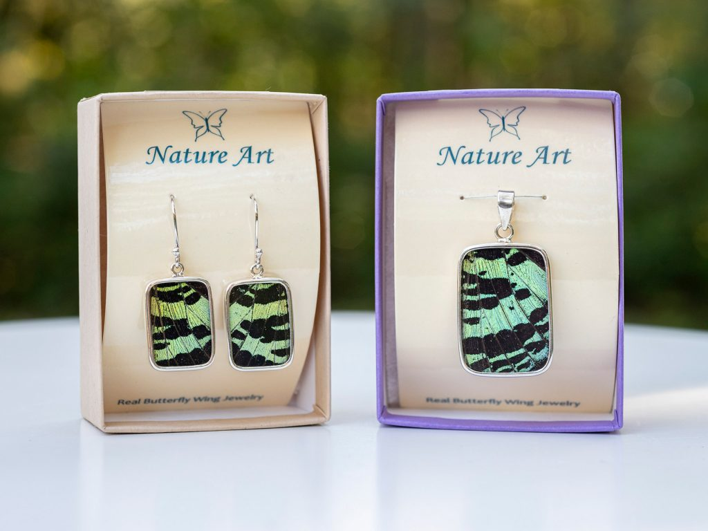 two jewelry items with iridescent butterfly wings embedded
