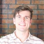 Nick Homziak in front of brick wall.