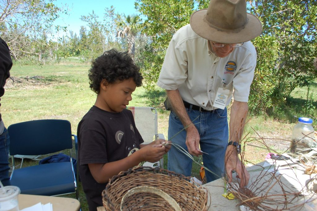 child learning basket weaving from adult
