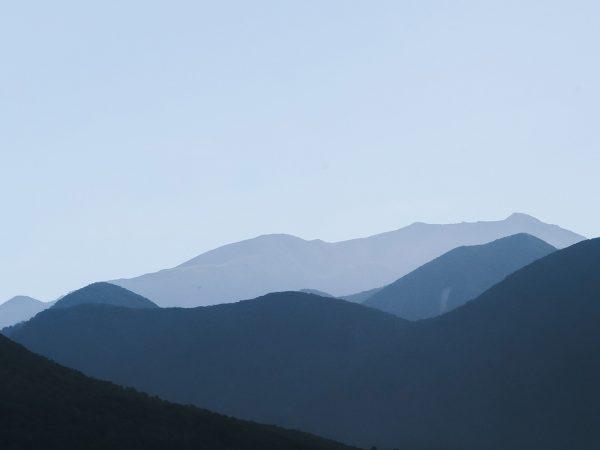 shadowed mountain range against light sky