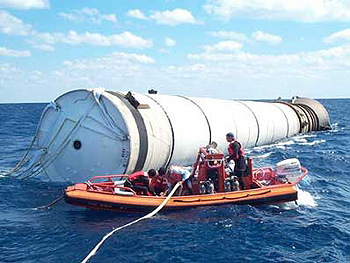 workers retrieve rocket boosters