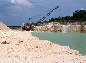 dragline scooping limestone in dig site