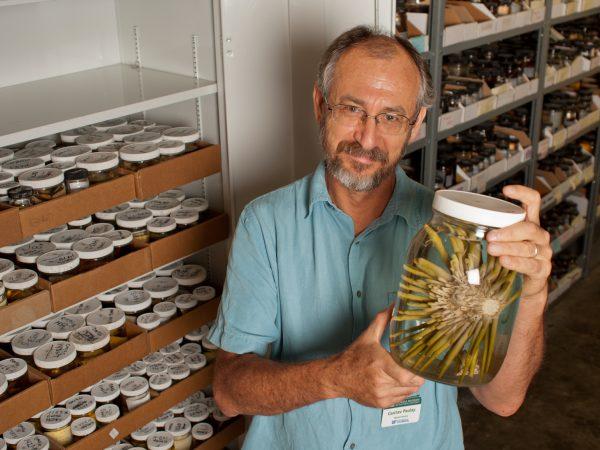 Gustav Paulay holds a spiny invertebrate specimen in a jar