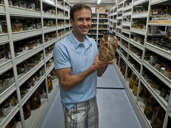 Rob Robins holding large jar in collection aisle