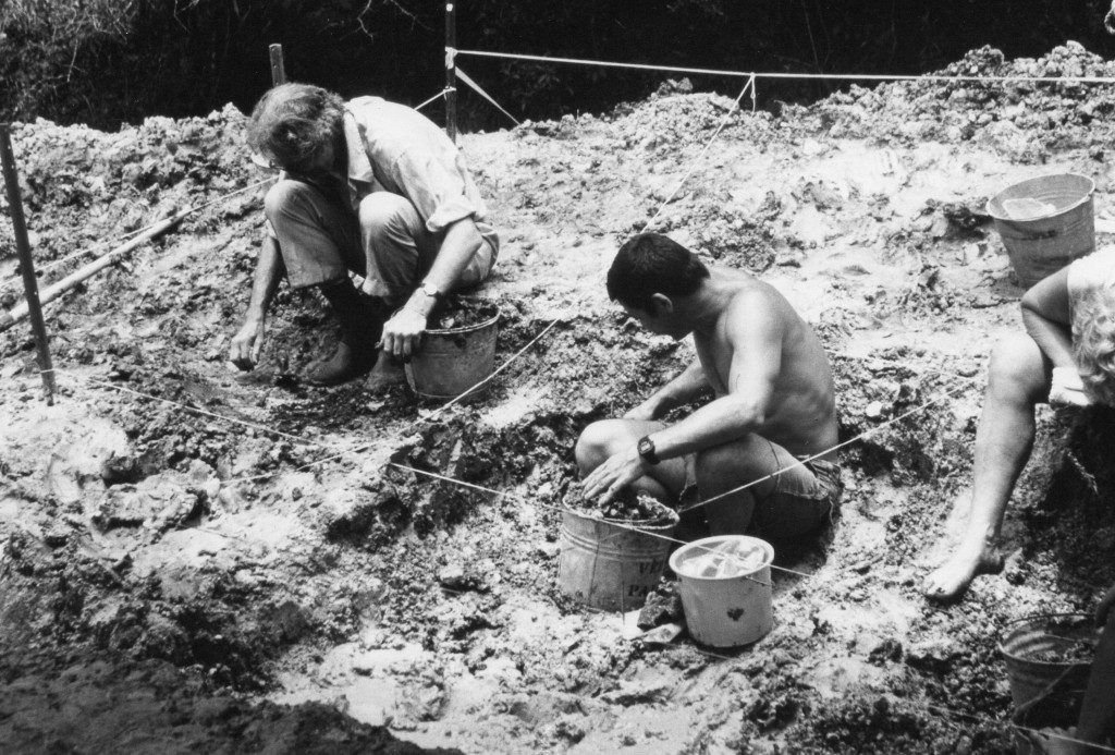 three researchers digging at the site in a black and white photo