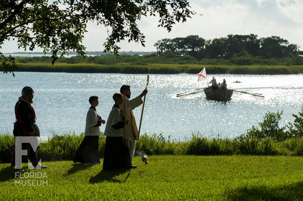 procession with small boat in the background