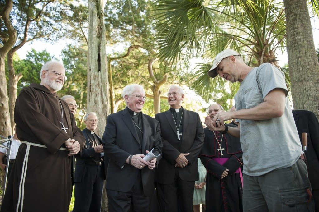 Waters shows a newly found artifact to a group of priests