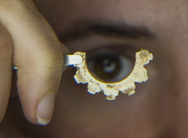 Museum doctoral examines a piece of marine shell made into an ornament.