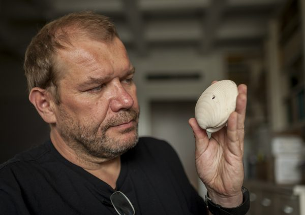 Researcher Michal Kowalewski holds a fossil shell bearing the mark from a drilling predator