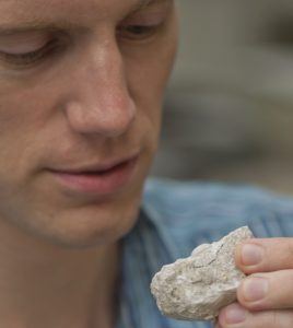 Researcher holds fossil crustacean
