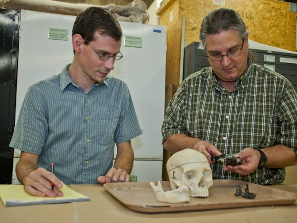 Two researchers examine a skull on a table