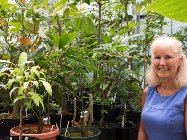 smiling woman next to potted plants