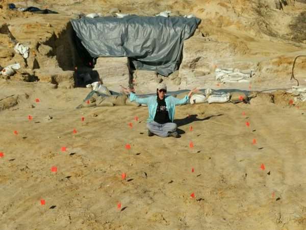 A scientist poses at a fossil site
