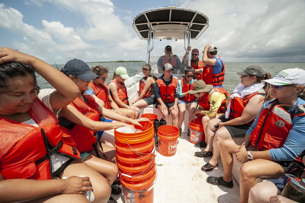 Students and researchers sit in a boat.