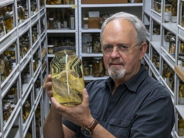 man holding specimen jar